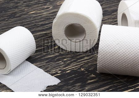 Rolls of toilet paper on black  wooden board