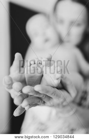 Blurred black and white image of a mother holding baby's feet on her hands