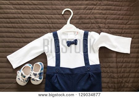 Closeup of an elegant suit for baby boy and a pair of booties