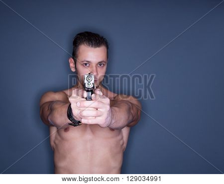Closeup of a undressed man pointing gun to the camera