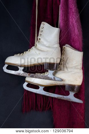 White ice skates hanging with red and pink wool scarf
