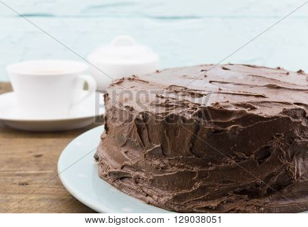Chocolate cake whole close up on blue plate with rustic wood background