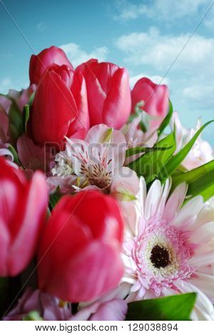 Lower angle of a flower bouquet with white gerbera and red tulips