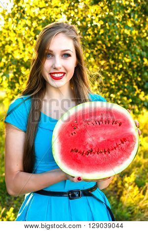 Smiling young blonde woman with long hair holding half of juicy watermelon