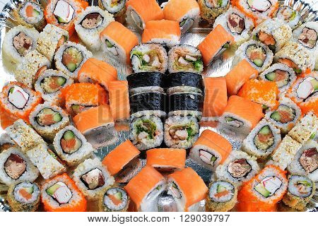 many fresh and tasty sushi rolls close up