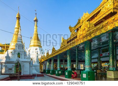 Yangon Myanmar - January 9 2012: A monk under the golden stupas of the Swedagon Pagoda.
