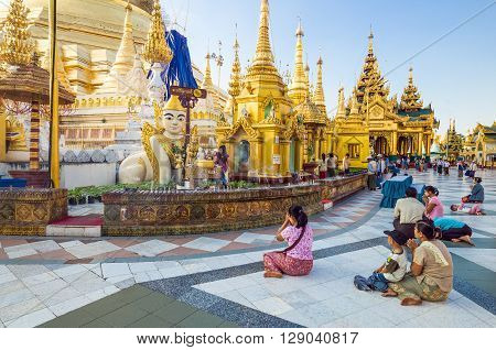 Yangon Myanmar - January 9 2012: Local religious people in prayer in the Swedagon Pagoda.
