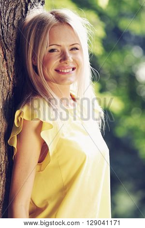 Beautiful happy young woman in summer park