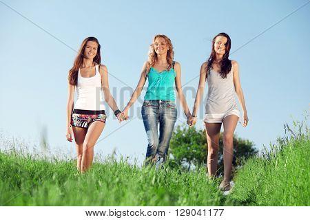 Three happy female friends walking on summer meadow