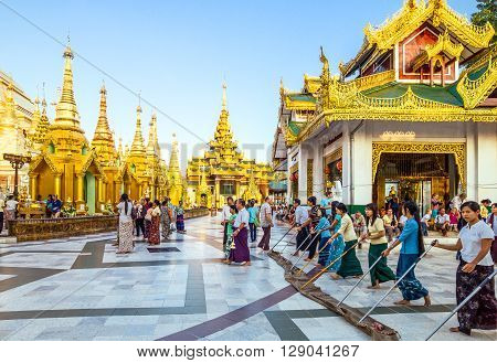Yangon Myanmar - January 9 2012: Young local religious cleaning the floor of the Swedagon Pagoda.