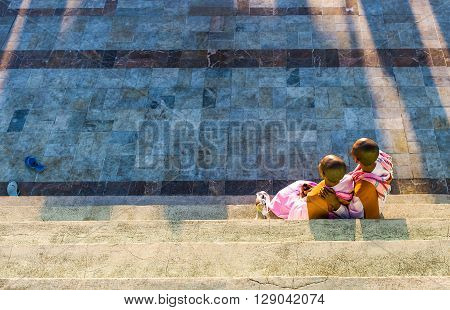 Kyaikhto Myanmar - January 10 2012: Two young monks on a terrace of the sacred Buddhist mountain