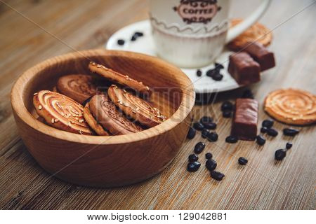 There are Cookies,Candy Chocolate Peas,Poppy;Porcelain Saucer and Cap with Coffee,Tasty Sweet Food on the Wooden Background,Toned