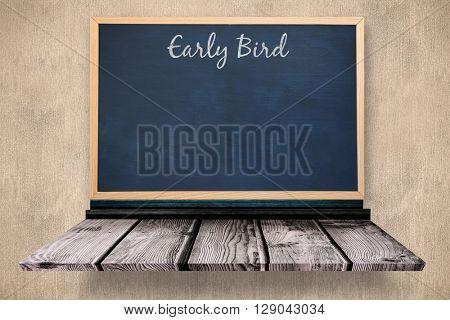 Early bird message against blackboard on a wooden shelf