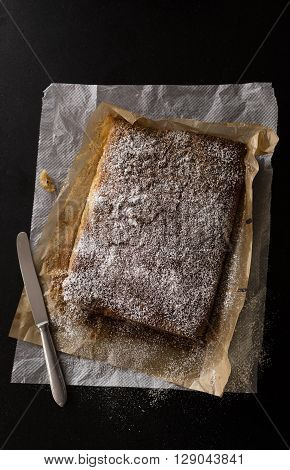 almond cake just baked with powdered sugar on a black stone kitchen table