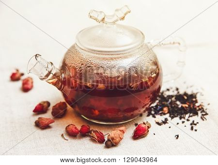 The Dry Red Small Roses with Black Tea in the Glass Teapot,Tea Drinking,Aromatized Flowers,Table Rough Linen Cloth;Toned