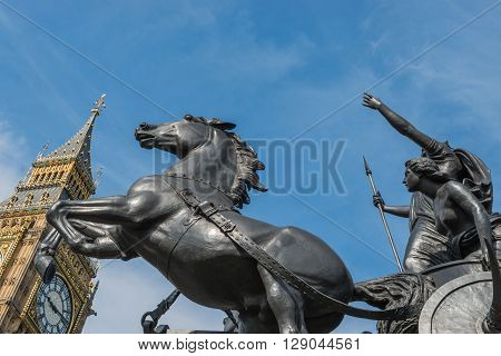 Statue of Queen Boudicca in the morning sunshine beside 'Big Ben', Houses of Parliament, London. Boudicca was the Queen of the Iceni tribe led a revolt against the Roman occupation of Britain.