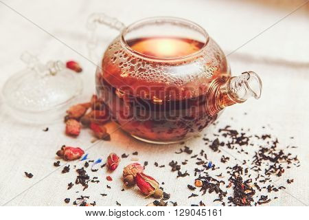 The Dry Red Small Roses with Black Tea in the Glass Teapot,Tea Drinking,Aromatized Flowers Linen Tablecloth;Toned