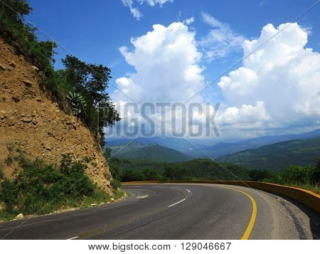 abrupt turn of the mountain road under cloudy sky clear summer warm sunny day