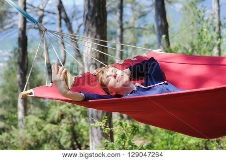 Young smiling girl enjoy in red hammock in forest. Relaxing on hammock with a smartphone. Redhead woman with freckles closed her eyes in pleasure. Forest, mountains in the background.