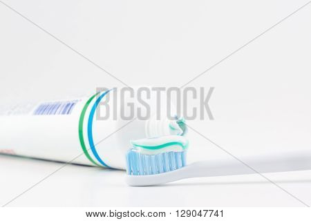 toothpaste tube with a small amount of toothpaste on a toothbrush