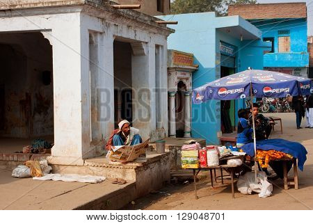 VARANASI, INDIA - JAN 3, 2013: Asian trader reads the morning newspaper in front of his place of sale on January 3, 2013 in Varanasi India. The literacy rate in the Varanasi urban agglomeration is 77 perc.