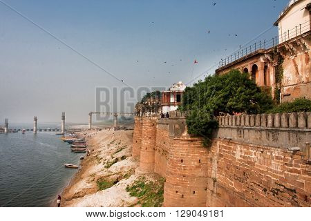 VARANASI, INDIA - JANUARY 3, 2013: Ganges river near the huge historical walls of Ramnagar Fort on January 3, 2013. The Ramnagar Fort of Varanasi was built in 1750 in typical Mughal style of architecture