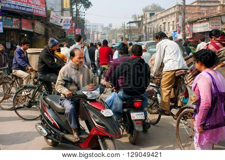 VARANASI, INDIA - JANUARY 1, 2013: Motorcycle drivers cyclists and pedestrians move on the busy crowded street at the morning on January 1, 2013. Varanasi urban agglomeration had a population of 1435113