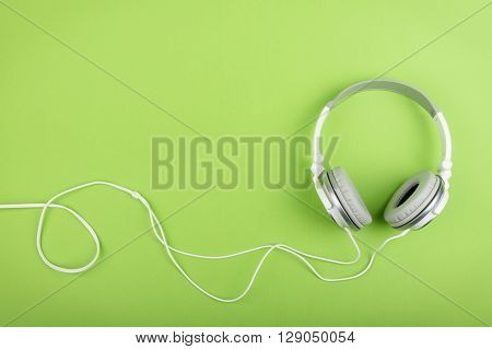 close up of Headphones on green background.