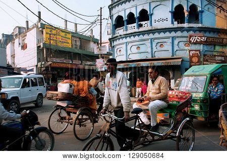 LUCKNOW, INDIA - JAN 31, 2013: Rickshaw drives through the crowded street with many bikes on January 31, 2013 in Lucknow India. Lucknow with population of 6000455 is the largest city of Uttar Pradesh.
