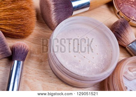Face makeup cosmetics on a light wooden floor - brush powder blush foundation.