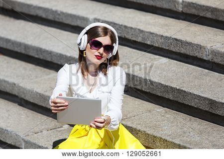 Teen student girl or young woman listens to the music from tablet pc in earphones. Girl wears sunglasses sitting on the stairs in downtown. Internet, music and modern technologies leisure concept.