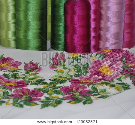 cross-stitch flower ornament on a background of colorful spools of thread