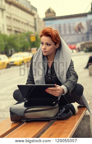 Young woman on a street bench with laptop. Young beautiful woman sitting on a bench on the street with laptop