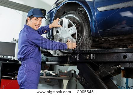 Confident Mechanic Fixing Hubcap To Car Tire
