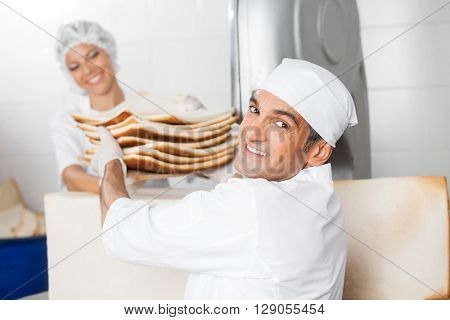 Smiling Baker Receiving Bread Waste From Coworker