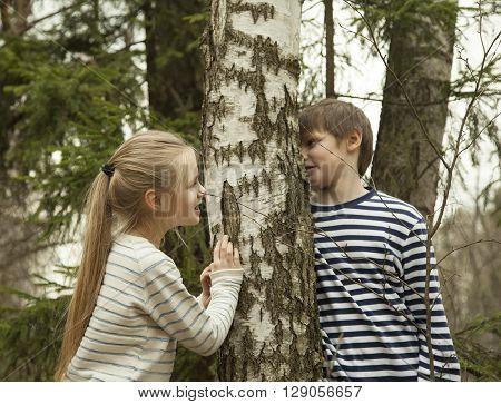 cute girl and boy walking in a birch grove