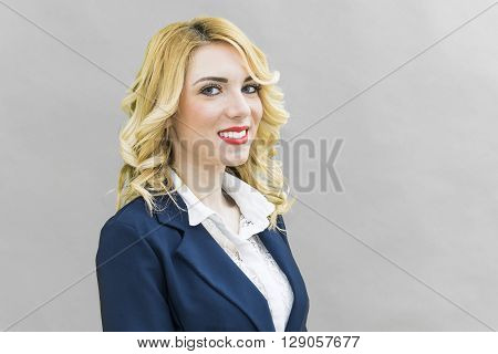 Portrait of Young woman in suits. Wearing blue suit she has blonde hair and blue or blue eyes on a white background. Smile always smiling.