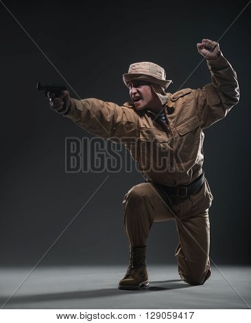 Soldier With A Gun Takes Aim On Dark Background