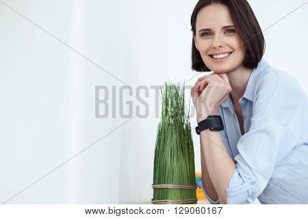 Attractive girl is standing and leaning on small table near plant at home. She is smiling and looking at camera with anticipation. Copy space in left side