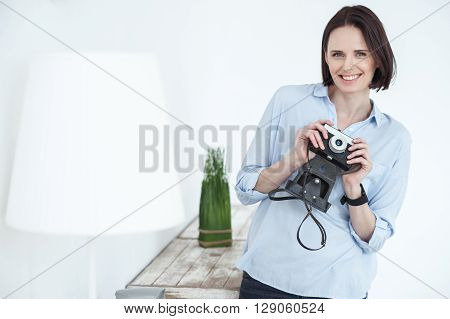 Beautiful female photographer is standing and holding a camera at home. Woman is looking forward and smiling
