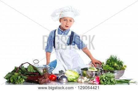 Cute boy in chef's hat with big ladle, casserole, and fresh vegetables over white background