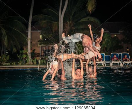 Varadero island, Rock Arenas Dora-dos, Cuba, Aug 10, 2014, fragment of view of amazing beautiful professional dancers performing the water show in outdoor swimming pool at night