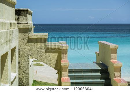 Fragment of an old antique vintage steps attached to the building wall against tranquil azure ocean and blue sky background