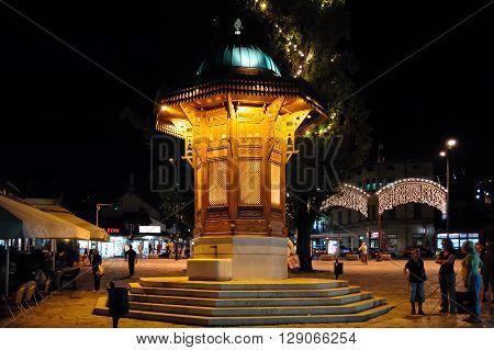 SARAJEVO BOSNIA AND HERZEGOVINA - SEPTEMBER 4 2009: The Sebilj wooden water fountain (Sebil) illuminated at night