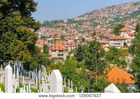 SARAJEVO BOSNIA AND HERZEGOVINA - SEPTEMBER 4 2009: Alifakovac cemetery tombstones and view of the old Vratnik town