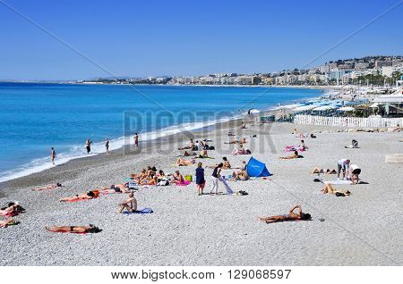 NICE, FRANCE - MAY 16: People sunbathing on the beach on May 16, 2015 in Nice, France. The long and famous seafront of Nice bordering the Mediterranean Sea is known as the Promenade des Anglais
