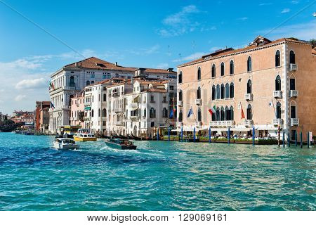 VENICE, ITALY - 17 OCTOBER 2015: Boat traffic in the Grand Canal, Venice, Italy passing in front of the historic 15th century palazzo housing the five star Gritti Hotel. October 17 2015.