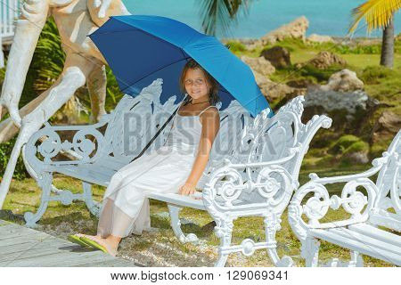 Stylish joyful little girl sitting in tropical garden on metal white vintage bench and holding blue big umbrella on sunny hot day against ocean background