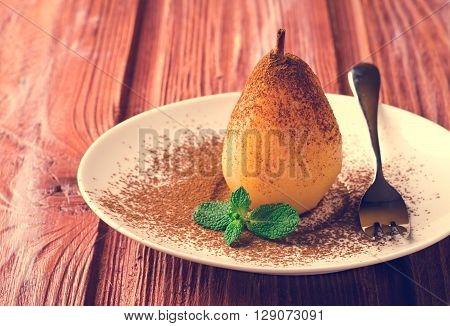 Poached pears with cocoa and mint on white plate, wooden background
