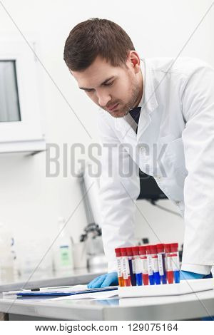 Skillful male researcher is analyzing experiment in laboratory. He is reading documents seriously. Man is standing near a set of flasks